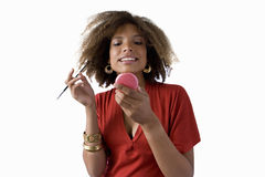 young woman looking in mirror applying makeup, cut out Stock Image