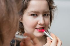 Young woman is looking in mirror and applying red glossy lipstick on her lips Royalty Free Stock Photo