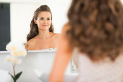 Young woman looking in mirror in bathroom stock image