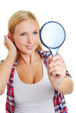 Young woman looking into mirror. Young blond happy woman looking into a hand mirror Stock Photo