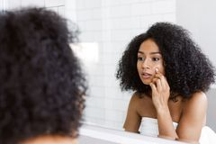 A young woman looking at mirror. And examines her skin, touching face with finger Royalty Free Stock Photos