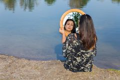 Woman looking in mirror at water. Young woman looking at mirror image near water Stock Images