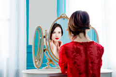 Young woman looking at mirror. Portrait of beautiful young woman looking at herself in the wonderful mirror and sitting next to it Stock Images