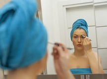 Young woman looking in the mirror and putting make-up on Royalty Free Stock Photos
