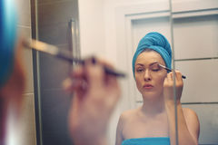 Young woman looking in the mirror and putting make-up on Royalty Free Stock Images