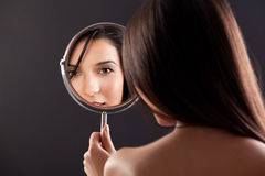 Young woman looking into a mirror, smiling. royalty free stock photo