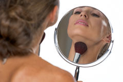 Young woman looking in mirror and using brush Stock Photos