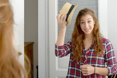 Young woman looking in a mirror. A young woman looking in a mirror Stock Image