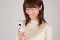 Young woman looking at mobile phone. Young Asian woman looking at mobile phone Stock Image