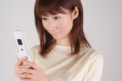 Young woman looking at mobile phone. Young Asian woman looking at mobile phone Royalty Free Stock Photography