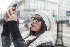 Young woman looking at mobile phone Royalty Free Stock Photos
