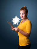 Young woman looking at modern tablet with abstract cloud Royalty Free Stock Photos