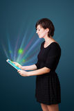 Young woman looking at modern tablet with abstract lights Stock Images