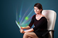 Young woman looking at modern tablet with abstract lights Royalty Free Stock Photo