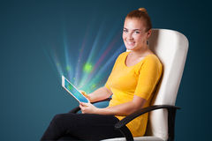 Young woman looking at modern tablet with abstract lights Stock Photo