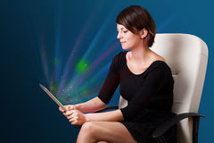 Young woman looking at modern tablet with abstract lights Stock Photos