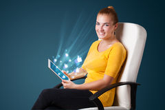 Young woman looking at modern tablet with abstract lights and so Royalty Free Stock Image