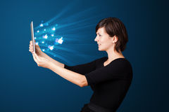 Young woman looking at modern tablet with abstract lights and so Royalty Free Stock Photo