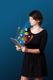 Young woman looking at modern tablet with abstract lights and va Stock Images