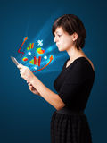Young woman looking at modern tablet with abstract lights and va Royalty Free Stock Photo