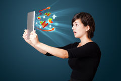 Young woman looking at modern tablet with abstract lights and va Stock Photography