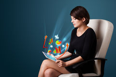 Young woman looking at modern tablet with abstract lights and va Royalty Free Stock Images