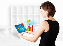 Young woman looking at modern tablet with colourful diagrams Royalty Free Stock Photo