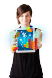 Young woman looking at modern tablet with colourful diagrams Royalty Free Stock Photography