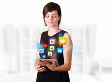 Young woman looking at modern tablet with colourful icons Stock Image