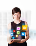Young woman looking at modern tablet with colourful icons Stock Photos