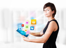 Young woman looking at modern tablet with colourful icons Royalty Free Stock Photography