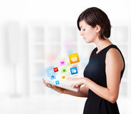 Young woman looking at modern tablet with colourful icons Royalty Free Stock Photo