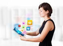 Young woman looking at modern tablet with colourful icons Royalty Free Stock Images