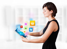 Young woman looking at modern tablet with colourful icons Stock Photo