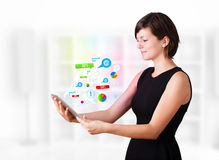 Young woman looking at modern tablet with colourful technology i Stock Image
