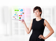 Young woman looking at modern tablet with colourful technology i Stock Photography