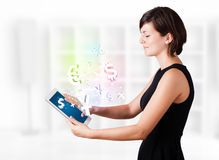 Young woman looking at modern tablet with currency icons. Young business woman looking at modern tablet with currency icons Royalty Free Stock Images