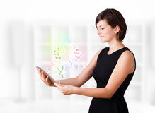 Young woman looking at modern tablet with currency icons. Young business woman looking at modern tablet with currency icons Stock Photos