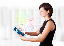 Young woman looking at modern tablet with currency icons. Young business woman looking at modern tablet with currency icons Royalty Free Stock Image
