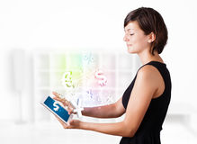 Young woman looking at modern tablet with currency icons Stock Photography
