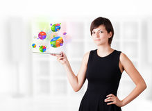 Young woman looking at modern tablet with pie charts Royalty Free Stock Image