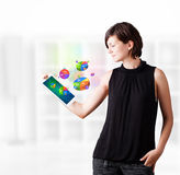 Young woman looking at modern tablet with pie charts Royalty Free Stock Images