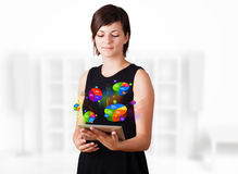 Young woman looking at modern tablet with pie charts Royalty Free Stock Photography