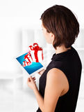 Young woman looking at modern tablet with present boxes Stock Image