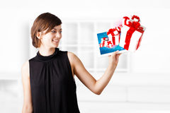 Young woman looking at modern tablet with present boxes Stock Photography