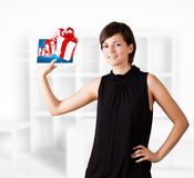 Young woman looking at modern tablet with present boxes Royalty Free Stock Images