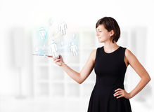 Young woman looking at modern tablet with social icons Royalty Free Stock Images