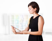 Young woman looking at modern tablet with social icons Stock Image