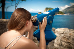 Young woman looking on mountain through touristic telescope Royalty Free Stock Photo