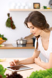 Young  woman looking for a new recipe for  cooking in a kitchen. Housewife is making online shopping by tablet comput Stock Photo